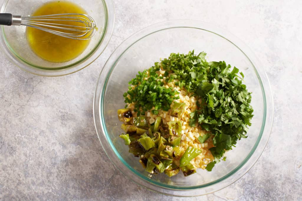 A bowl of lime dressing next to a bowl of ingredients for corn salad.