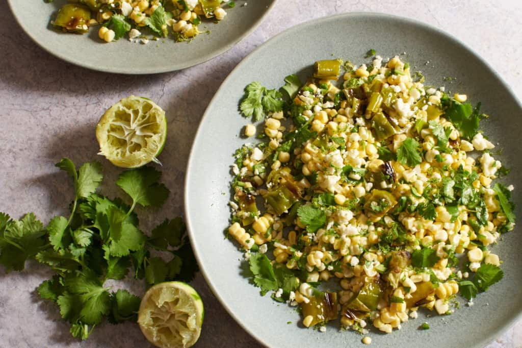 Fresh corn salad on gray plates next to cilantro and squeezed limes.