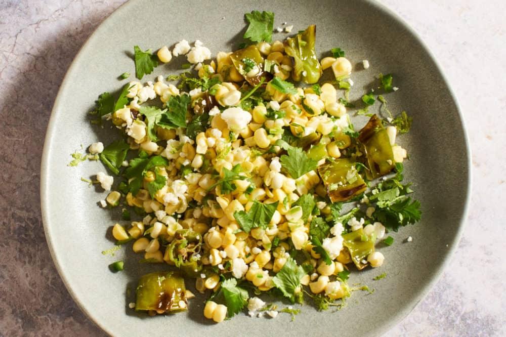 Fresh corn salad on a gray plate.