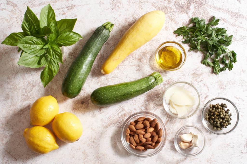 Zucchini, yellow squash, basil, parsley, lemons, and small bowls with capers, almonds, garlic and pecorino.