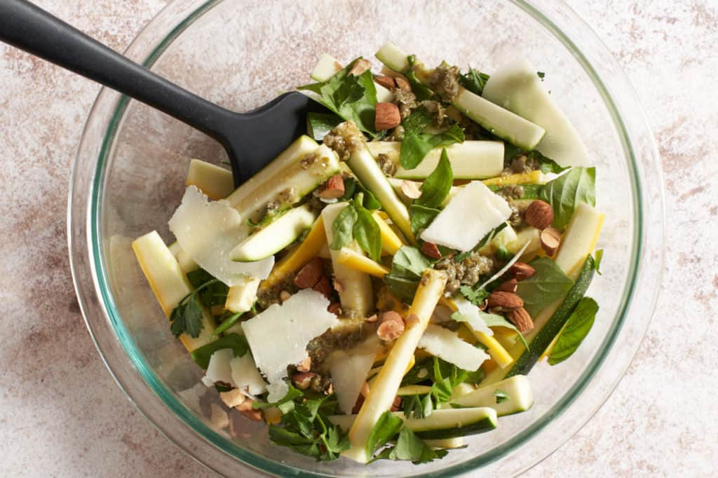 Zucchini salad ingredients in a glass bowl with a black spatula.