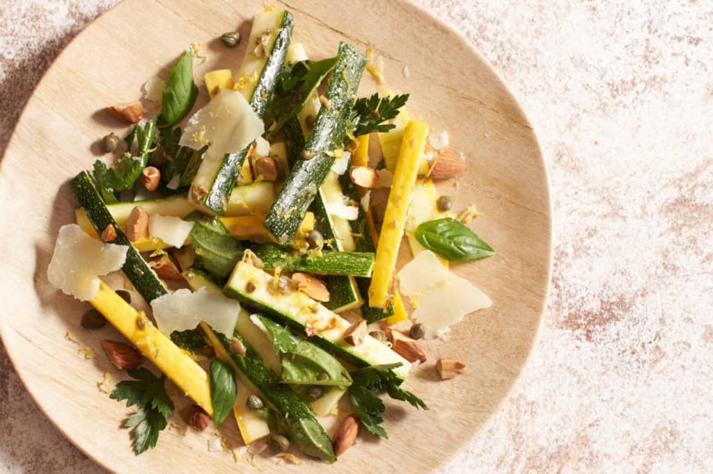 Zucchini salad on a tan plate.