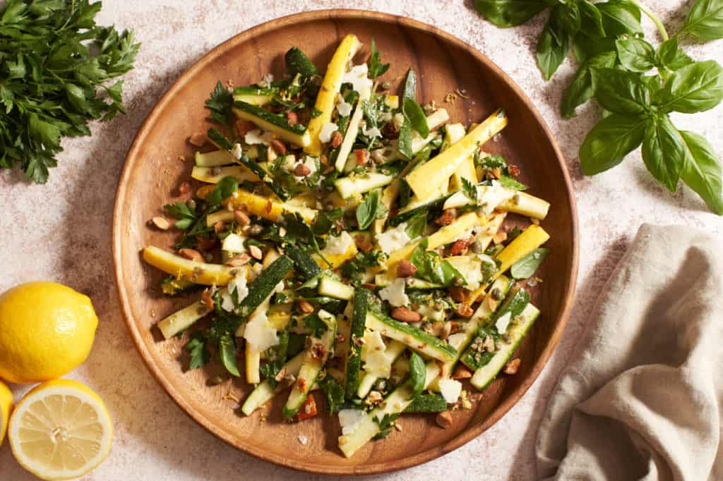 Zucchini salad on a wooden plate surrouned by herbs, lemons and a napkin.