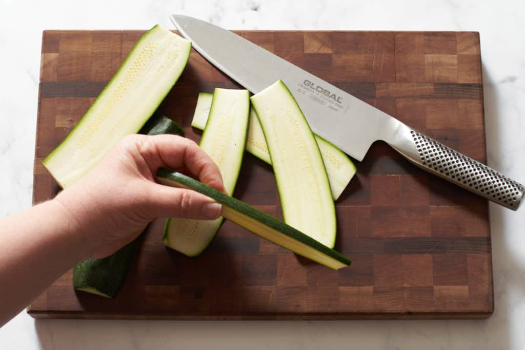 A woman's hand holding a slice of zucchini, a cutting board and knife are in the background.