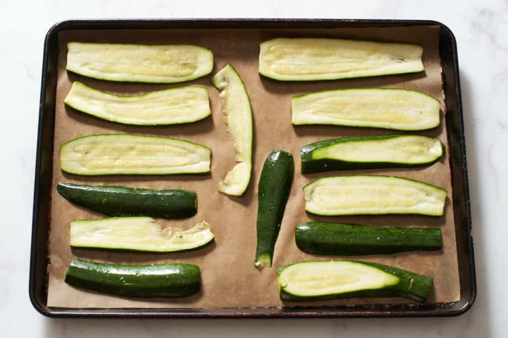 Raw sliced zucchini on a parchment lined sheet pan.