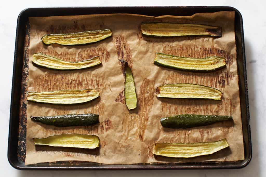 Roasted zucchini slices on a parchment lined baking sheet.