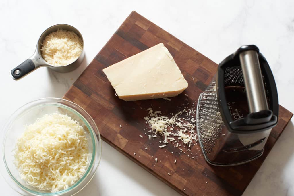 Parmesan cheese on a cutting board with a grater, a measuring cup and bowl full of cheese are to the left.