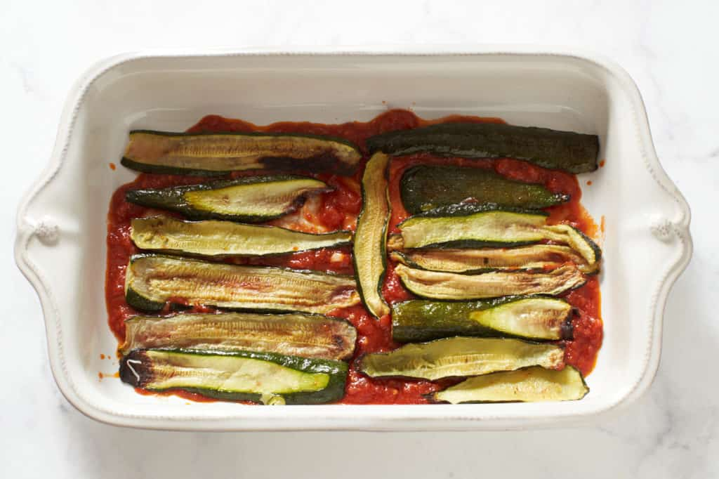Tomato sauce and roasted zucchini layered in a casserole dish.