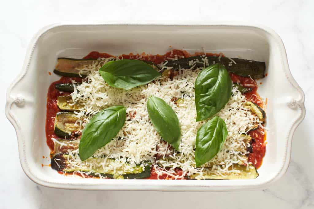 Tomato sauce and zucchini topped with parmesan cheese and fresh basil in a casserole dish.