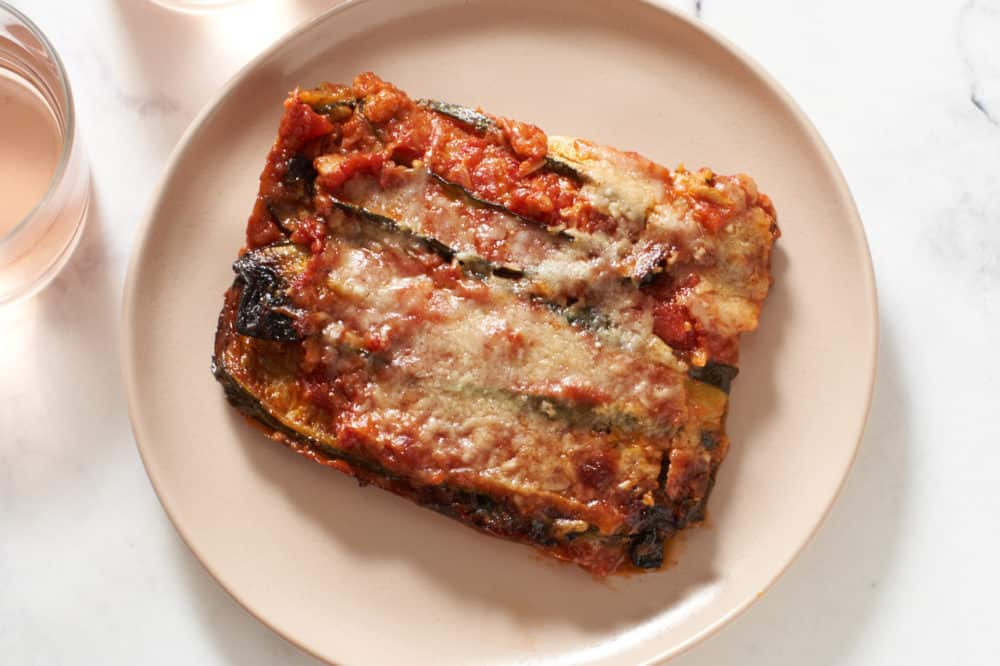 A slice of zucchini parmesan on a pink plate with a glass of rosé to the left.