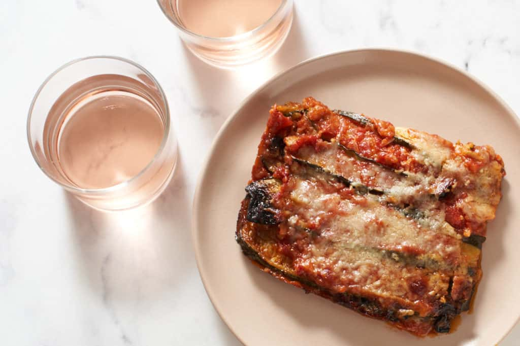 A serving of zucchini parmesan on a pink plate next to two glasses of rosé.