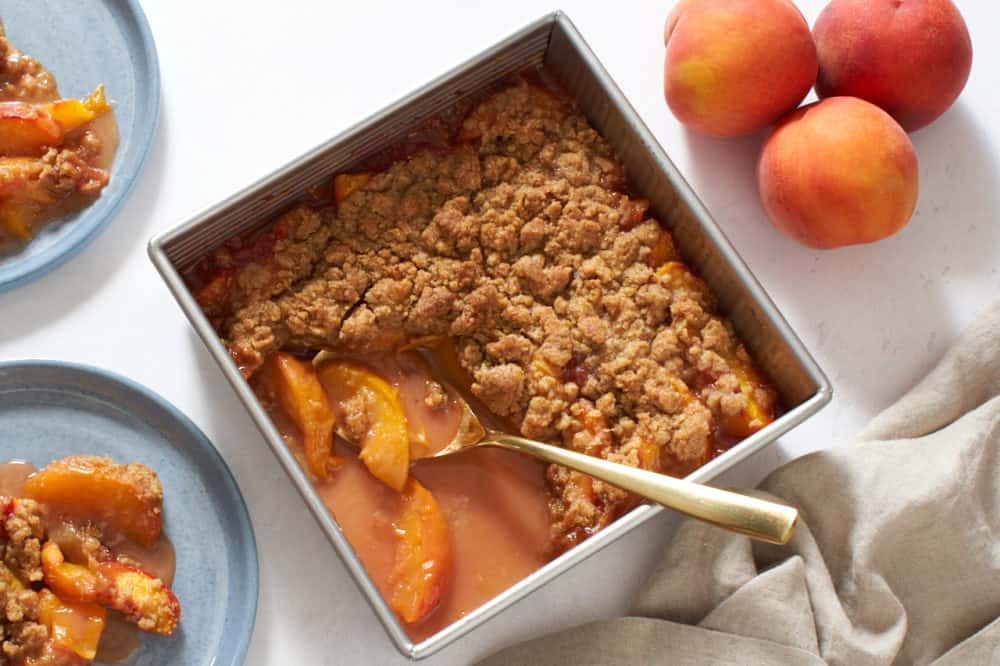 A square baking pan of peach crumble with a gold spoon in it surrounded by two blue plates of peach crumble, fresh peaches and a brown napkin.