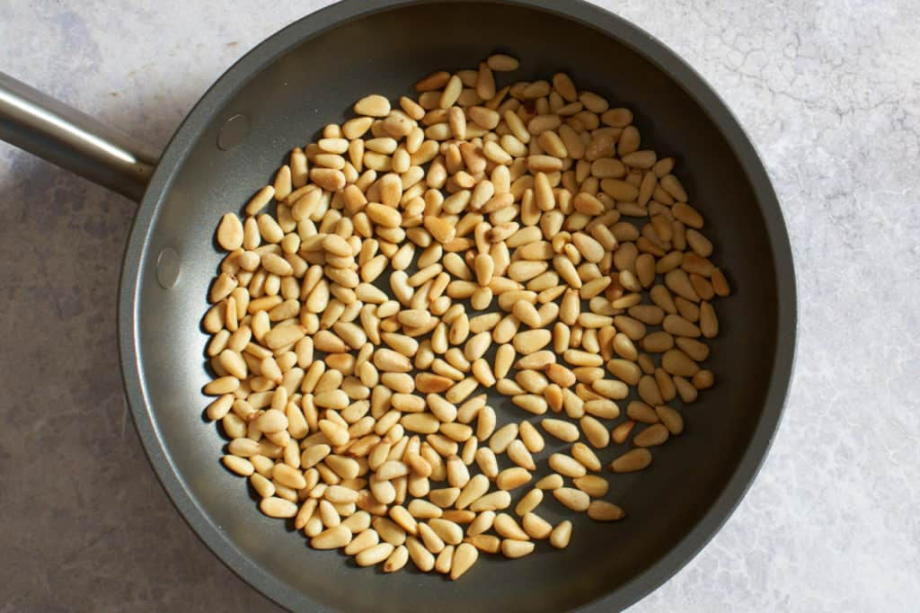 A small skillet with toasted pine nuts.