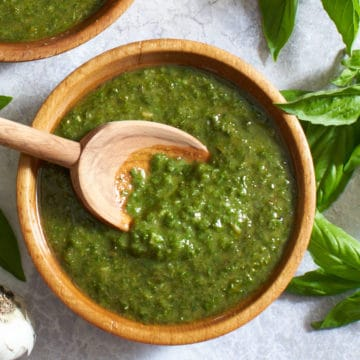 A wooden spoon in a bowl of pesto surrounded by fresh basil and garlic cloves.