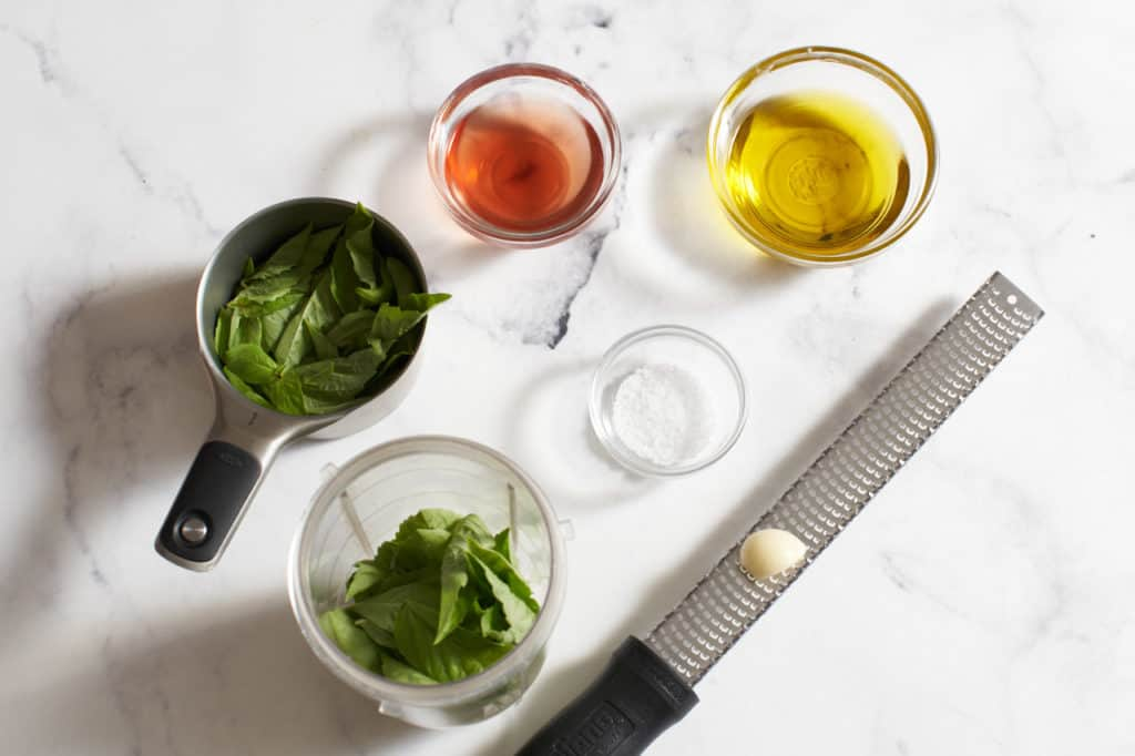 Small bowls with olive oil, salt, and red wine vinegar, a microplane grater with a garlic clove, a measuring cup of basil.