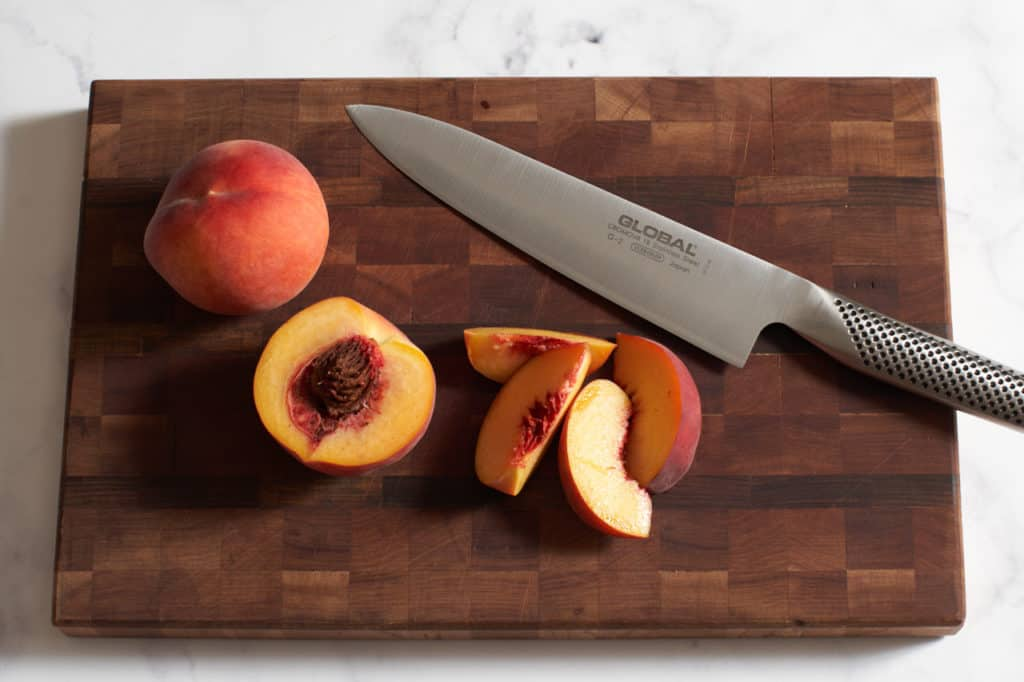 A knife on a wooden cutting board with sliced peaches.
