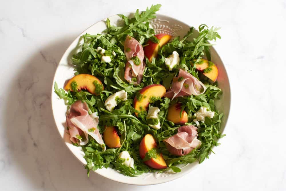 Peach salad in a white bowl.