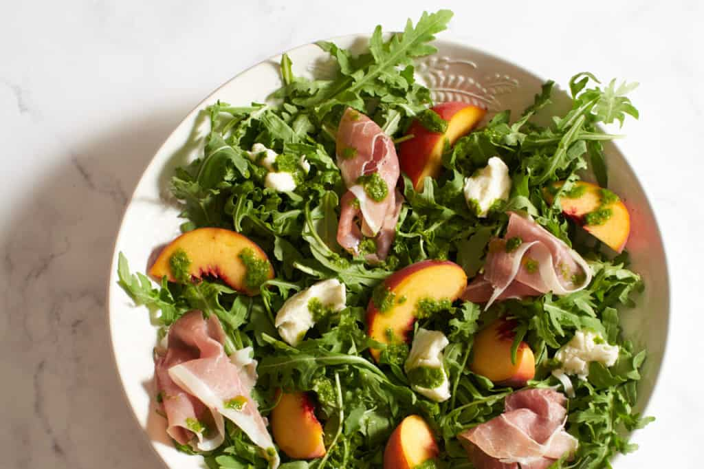 Peach salad in a white bowl on a marble surface.