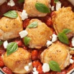 Chicken thighs with burst tomato sauce and goat cheese in a blue pan.