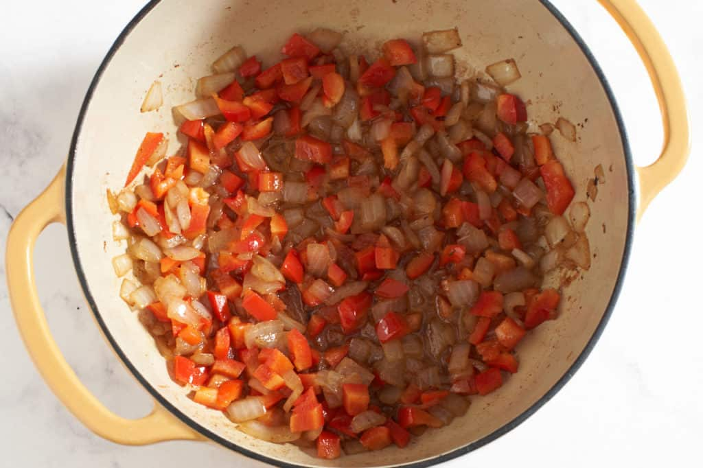 A dutch oven with sautéed red peppers and onions.