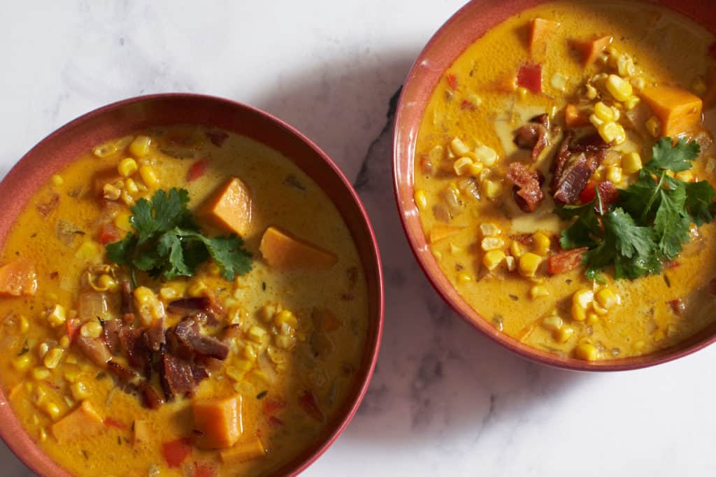 Two bowls of corn chowder with bacon and cilantro on top.