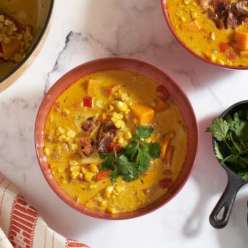 Two bowls and a pot full of corn chowder, two small skillets with cilantro and bacon are to the right.