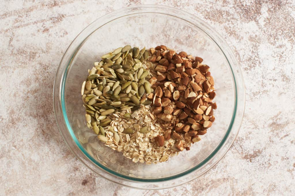 A glass bowl of oats, almonds and pumpkin seeds.