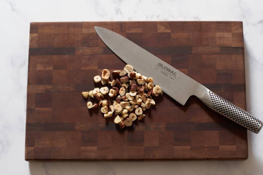 A knife on a cutting board with hazelnuts.