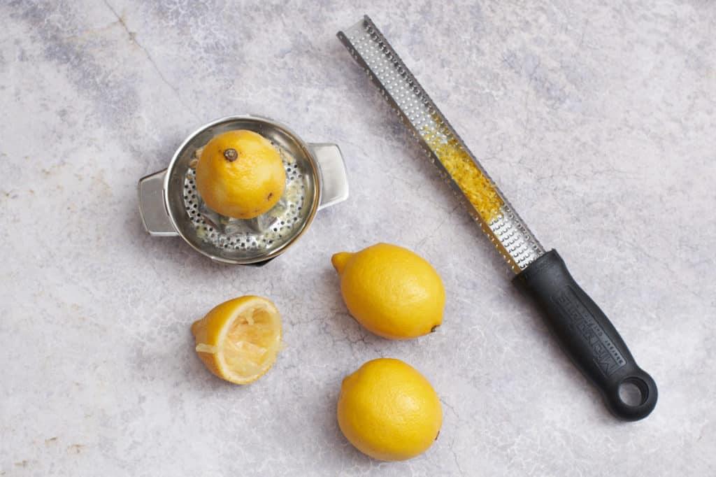 A juicer, a zester, and a few lemons.