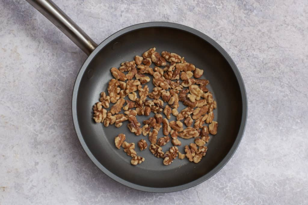 A small skillet with walnuts.