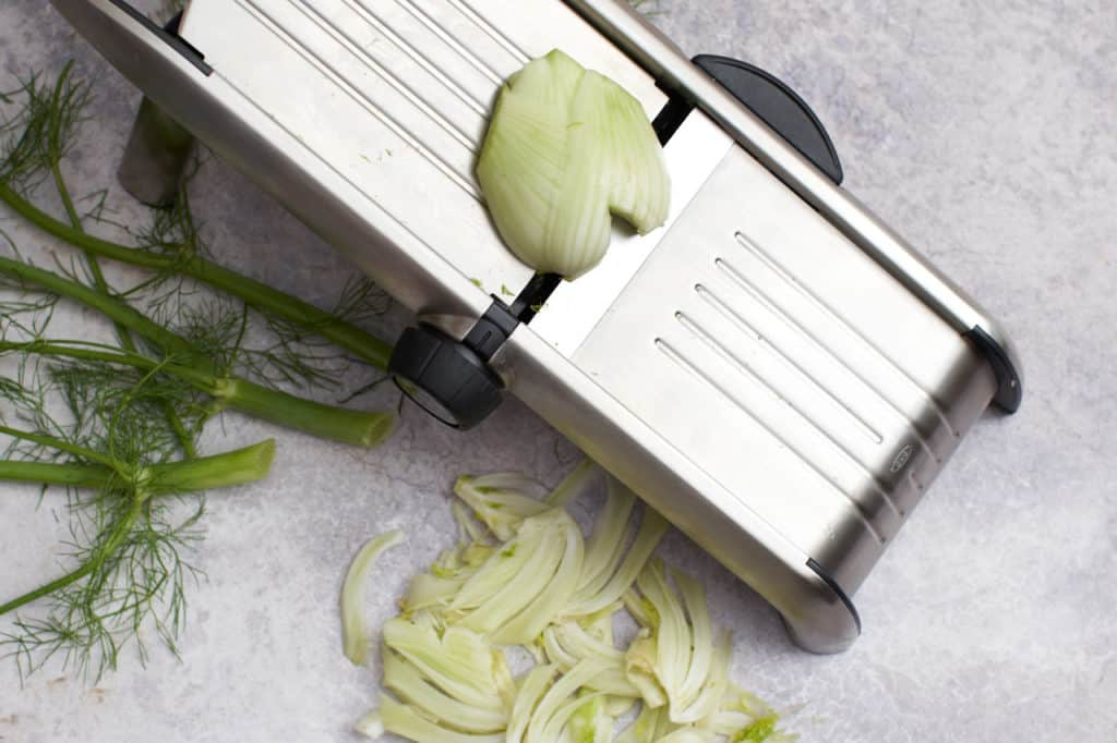 A mandoline with fennel slices.