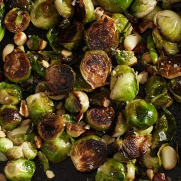 Crispy brussels sprouts in a cast iron pan with hazelnuts and garlic.