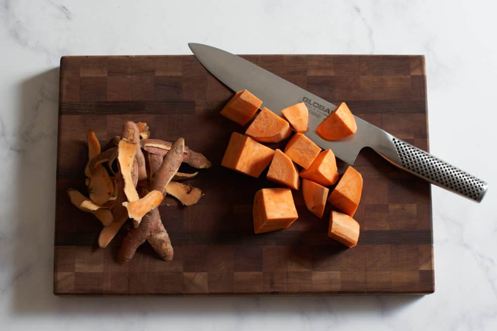 A knife on a wooden cutting board with chopped sweet potatoes.