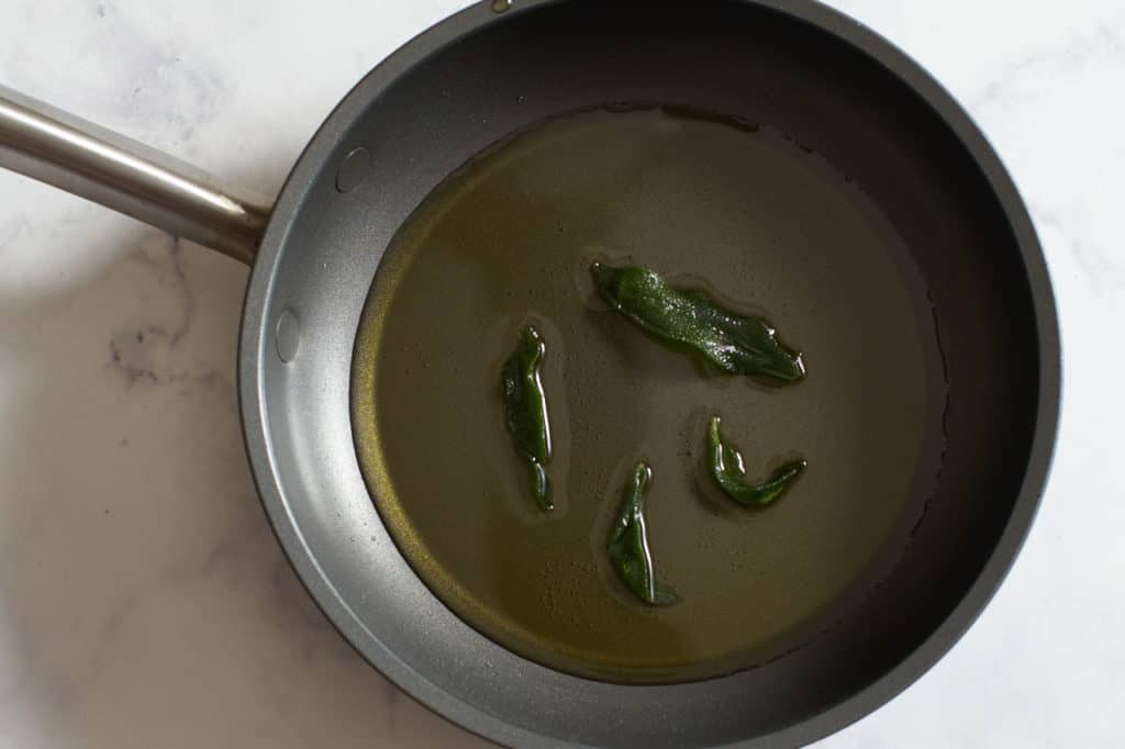 A small skillet with olive oil and fried sage leaves.