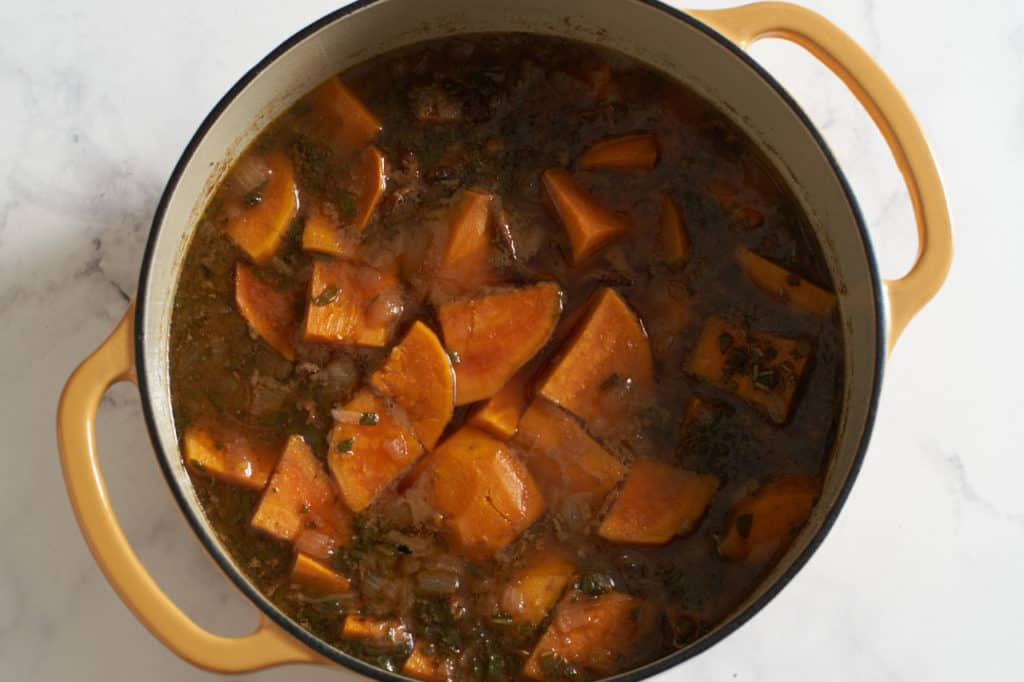 A dutch oven with broth and sweet potatoes.