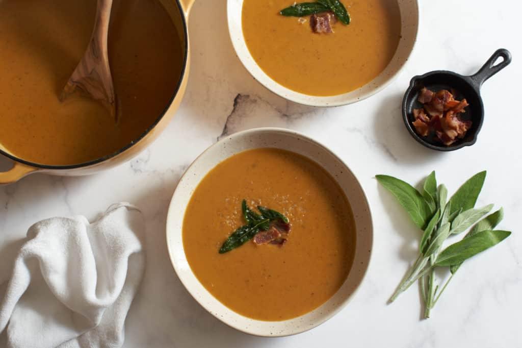 Two bowls and a pot of sweet potato soup.