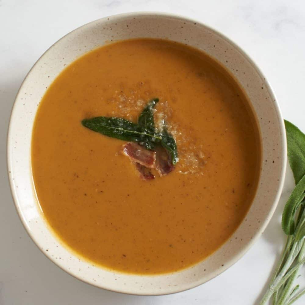 A bowl of sweet potato soup topped with bacon and fried sage leaves.
